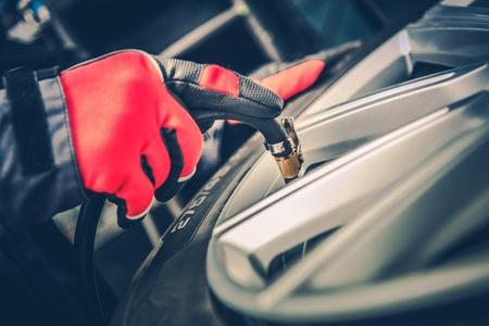 Tire Air Pressure Adjustment. Car Tires Maintenance. Closeup Photo.