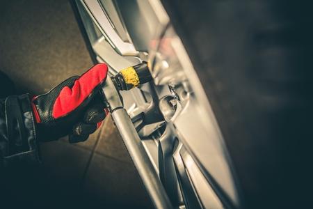 Vehicle Wheel Tire Change Closeup Photo. Removing Car Wheel Bolts. Reklamní fotografie