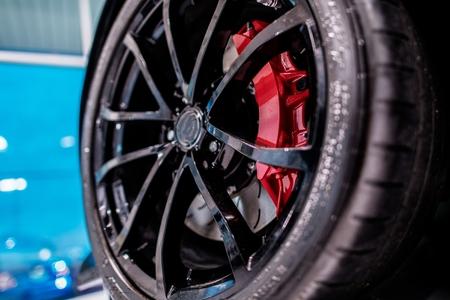 Black Alloy Wheel Closeup. Dealership Showroom Brand New Car. Automotive Theme.