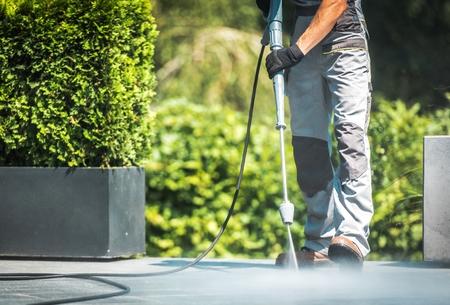 Patio Pressure Cleaning. Caucasian Men Washing His Concrete Floor Patio Using High Pressured Water Cleaner. Reklamní fotografie
