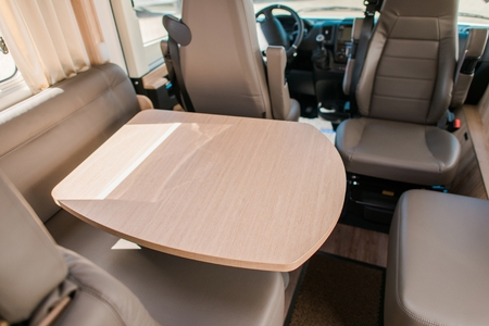 RV Camper Van Dinning Area with Wooden Table and Seats. Traveling in Style.