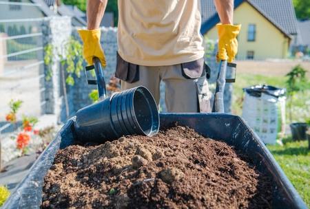 Caucasian Men Building Garden by Moving Soil in the Barrow. Gardening Theme. Reklamní fotografie