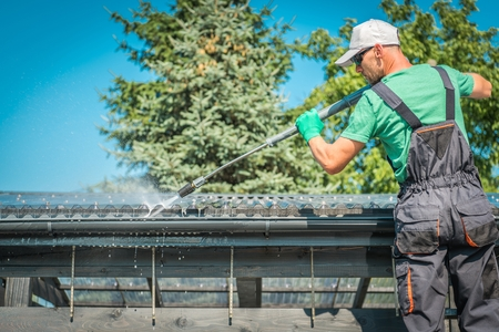 Roof and Gutters Power Cleaning Using Pressure Washer. Caucasian Worker.