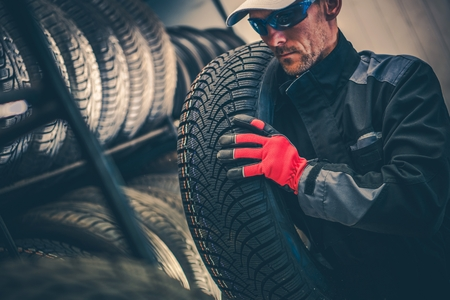 Auto Service Tire Replacement Theme. Caucasian Worker in His 30s Moving Winter Season Tire. Reklamní fotografie