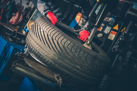 Car Tire Vulcanizing. Auto Service Worker and the Equipment. Reklamní fotografie