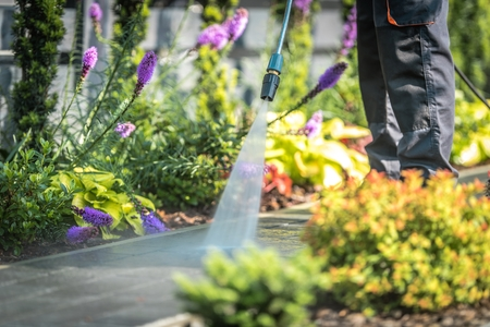 Power Washing Garden Cobble Stone Paths. Outdoor Cleaning Using Pressure Washer. Closeup Photo. Banco de Imagens
