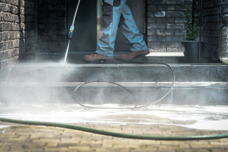 Pressure Washer Cleaning Time. Men Cleaning Outside House Stairs with Power High Pressured Cleaner. Ceramic Stairs and Home Entrance. Closeup Photo. Reklamní fotografie