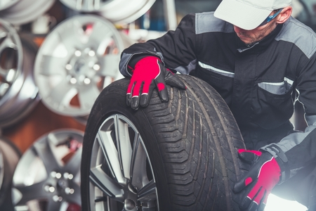 Replacing Car Tires and Alloy Wheels with New One. Caucasian Tire Service Worker with Large SUV Wheel.