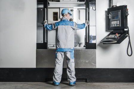 Large CNC Machine Operator. Caucasian Metalworking Worker In Front of the Machine. Reklamní fotografie