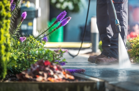 Backyard Garden Cleaning Time with Pressure Washer. Men Cleaning Garden Cobble Stone Path. Reklamní fotografie