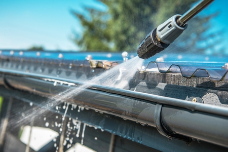 Spring Rain Gutters Cleaning Using Pressure Washer. Closeup Photo. Banque d'images - 106079760