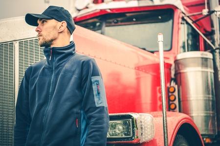 Tema de la industria de camiones y transporte terrestre. Conductor de camión semi americano caucásico delante de su camión de servicio pesado.