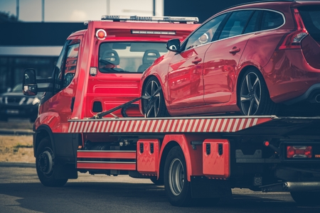 Red Broken Car on a Red Towing Truck. Closeup Photo. Vehicle Mechanical Problem on the Road.