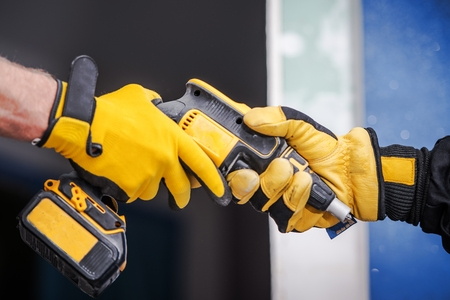 Sharing Construction Equipment Between Two Contractors in Safety Gloves. Closeup Photo. Drill Driver. Imagens
