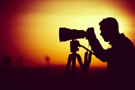 Golden Hour Photography. Silhouette of Men Taking Pictures with Large Telephoto Lens. Imagens