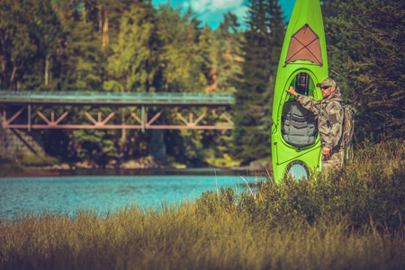 Camping with Kayak and Fly Fishing Time. Caucasian Men Preparing For Kayak Trip. Norway, Europe. Stock Photo