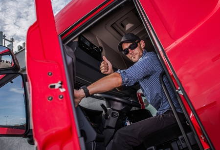 Happy Caucasian Semi Truck Driver Showing Thumb Up. Trucking Theme. Transport Industry. Reklamní fotografie