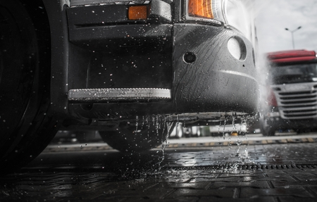 Pressure Washing Semi Truck Closeup Photo. Wet Tractor Bumper. Clean Vehicle Concept Photo. Stock Photo
