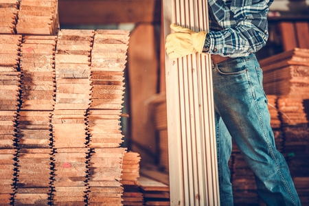 Contractor with Planks. Caucasian Carpenter with Pile of Wood Boards. Construction Materials Theme. Reklamní fotografie
