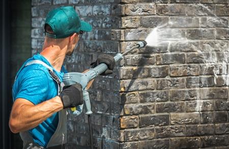 Lavado de la pared de ladrillo de la casa con lavadora a presión. Trabajador caucásico de unos 30 años. Foto de archivo