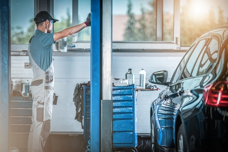 Auto Service Worker in Front of Heavy Duty Car Lift. Preparing For the Work. Automotive Industry. Reklamní fotografie