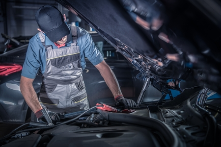 Car Mechanic Work. Caucasian Vehicles Technician Looking Under Car Hood Looking For the Existing Problem. Automotive Industry. Reklamní fotografie