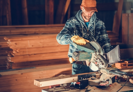 Woodwork Contractor Job. Caucasian Worker Cutting Wood Planks Using Circular Wood Saw. Construction Industry. Reklamní fotografie