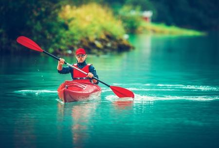 Glacial Lake Kayak Trip. Caucasian Tourist Paddling in the Red Kayak.