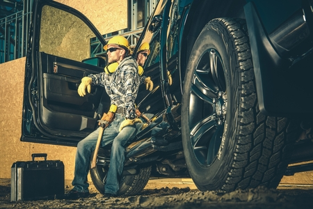 Caucasian Construction Industry Worker in His 30s Relaxing After Hard Working Day. Worker and His Black Pickup Truck. Industrial Theme. Reklamní fotografie