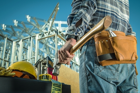 Caucasian Steel Construction Worker with Large Professional Hammer in Front of Construction Site. Reklamní fotografie
