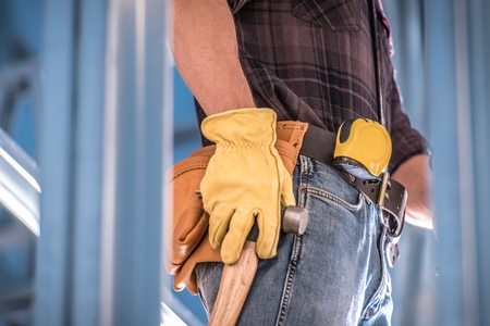 Getting Construction Job Concept Photo. Caucasian Worker with Tools Belt Large Hammer and Measuring Tape. Closeup Photo. Reklamní fotografie