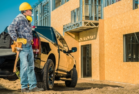 Residential Construction Site. Young Caucasian Contractor Worker in His 30s and His Pickup Truck in Front of Newly Constructed Building. Metal Frame and Plywood Walls.