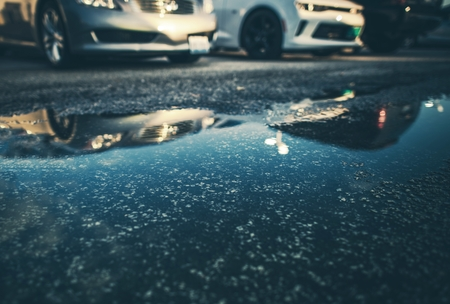 Water on the Road Concept Photo. Flooded Street Closeup.