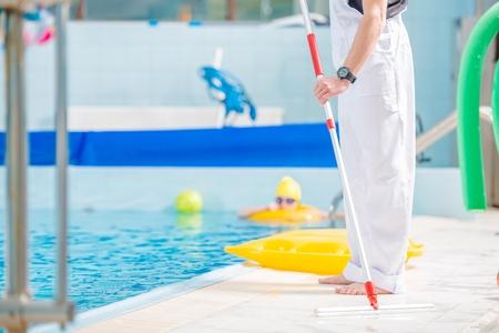 Swimming Pool Cleaner. Caucasian Worker Taking Care of the Pool. Zdjęcie Seryjne