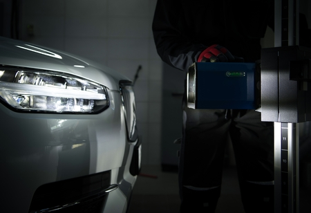 Headlight Aimer in Front of Modern Vehicle. Light Beam Test in the Professional Auto Service. Car Headlight Adjustment and Aim.