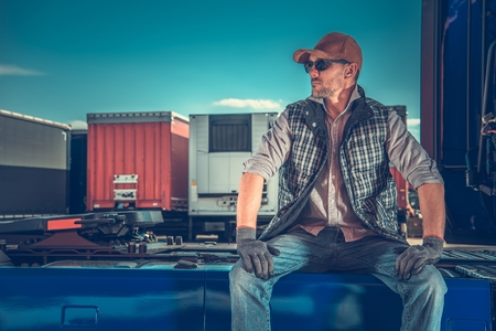 Truck Driver Rest Area. Parking For Truckers. Caucasian Men Taking Break and Seating on His Semi Tractor. Stock Photo