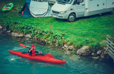 Waterfront RV and Tent Camping with Kayaking. Caucasian Sportsman in the Kayak on Glacial Lake.