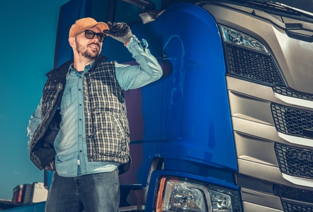 Conductor de camión semi y vehículo moderno de golpe. Feliz camionero caucásico de unos 30 años. Industria del transporte.