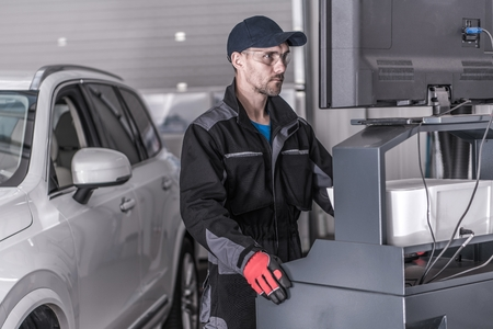 Auto Service Technician in Front of the Computer Analyzing Data From the Vehicle. Stockfoto