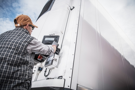 Refrigerated Semitrailer Cargo. Adjusting Temperature by Caucasian Truck Driver. Banque d'images