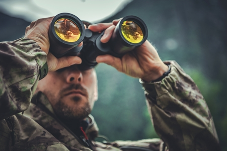 Caucasian Army Soldier in His 30s with Binoculars in Hands. Military Theme.