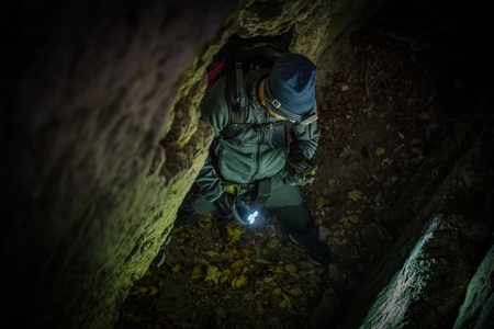 Caucasian Caves Explorer with Compass Device Looking For Right Way Outside. Reklamní fotografie