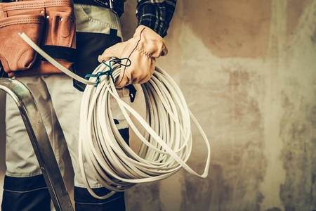 Electrician Contractor with Electric Cable Closeup Photo. Installing Whole New System. Reklamní fotografie