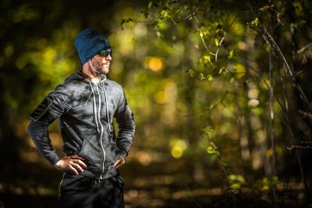 Caucasian Men in His 30s with Headphones on the Late Afternoon Jogging in the Forest. Outdoor Sportsman Runner.