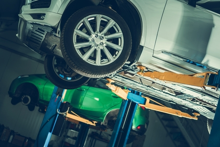 Automotive Industry. Modern Vehicles in the Auto Service Center. Repairing Cars on Lifts.