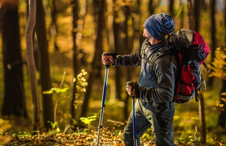 Caucasian Hiker in the Forest During Scenic Golden Fall Foliage. Men with Backpack on the Trailhead. Reklamní fotografie