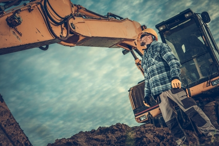 Excavator Operator at Work. Professional Ground Works Contractor and the Heavy Duty Construction Machinery.