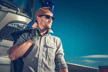 Relaxed Caucasian Truck Driver Wearing Baseball Hat and Sunglasses. Semi Truck in the Background. Reklamní fotografie