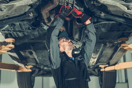 Car Mechanic Undercarriage Maintenance. Caucasian Worker Adjusting Tension on a Vehicle Drivetrain Elements.