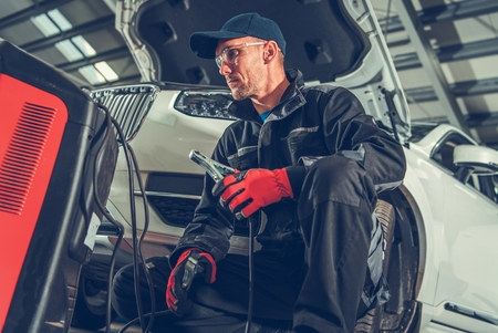 Caucasian Auto Service Worker Preparing Car Battery Jump Starter.